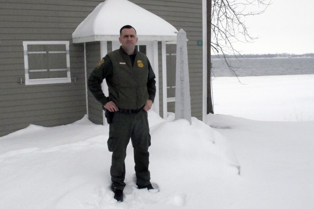 In this Monday Feb. 10, 2020, photo, U.S. Border Patrol Agent Dustin Judd poses near a border marker in Alburgh, Vt. Statistics show that the 295-mile...