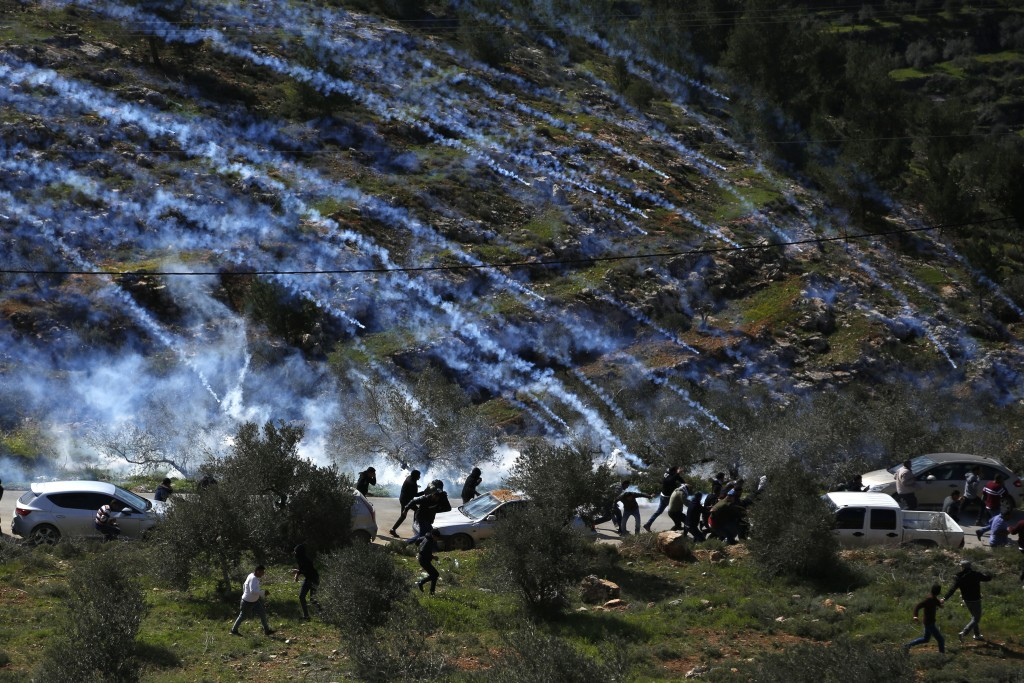 FILE - In this Feb. 28, 2020 file photo, Palestinian demonstrators run away from tear gas fired by Israeli forces during a protest against Israeli set...