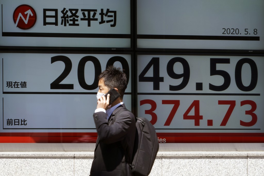 A man wearing a face mask to help curb the spread of the coronavirus walks past an electronic stock board showing Japan's Nikkei 225 index at a securi...