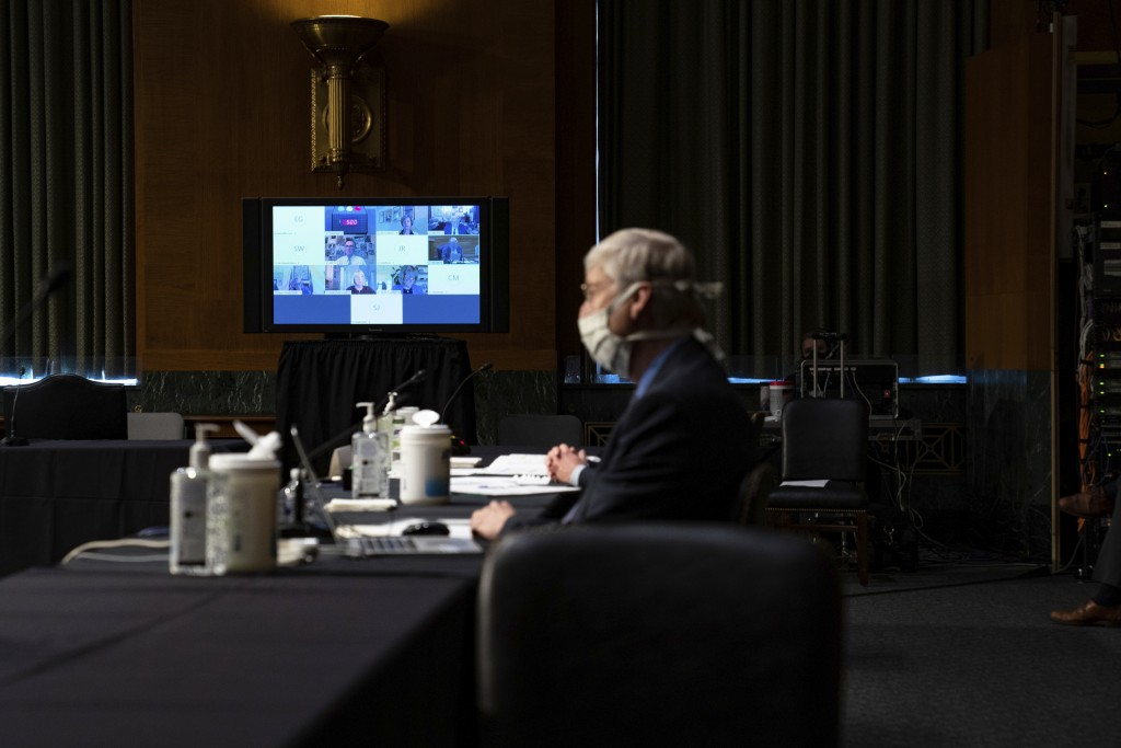 A monitor displays video feeds from members of the Senate Health Education Labor and Pensions Committee via teleconference during a Senate Health Educ...