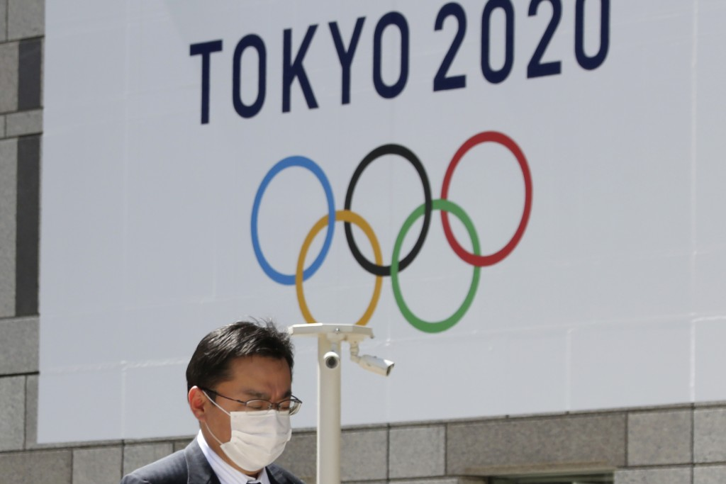 FILE - In this March 25, 2020, file photo, a man walks in front of a Tokyo Olympics logo at the Tokyo metropolitan government headquarters building in...