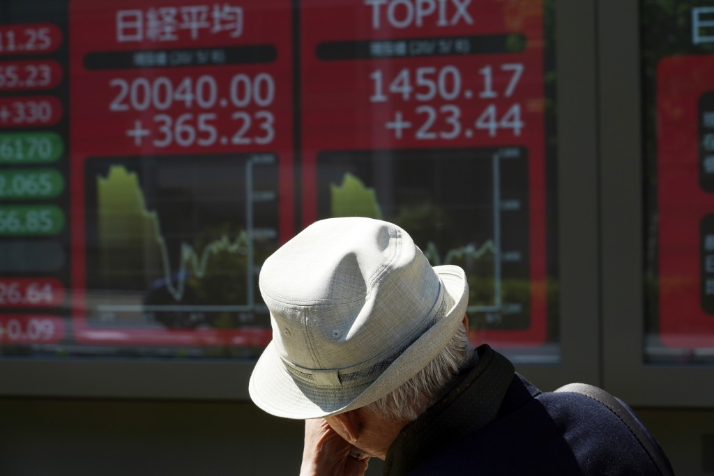 A man walks past an electronic stock board showing Japan's Nikkei 225 index at a securities firm in Tokyo Friday, May 8, 2020. Asian shares surged Fri...