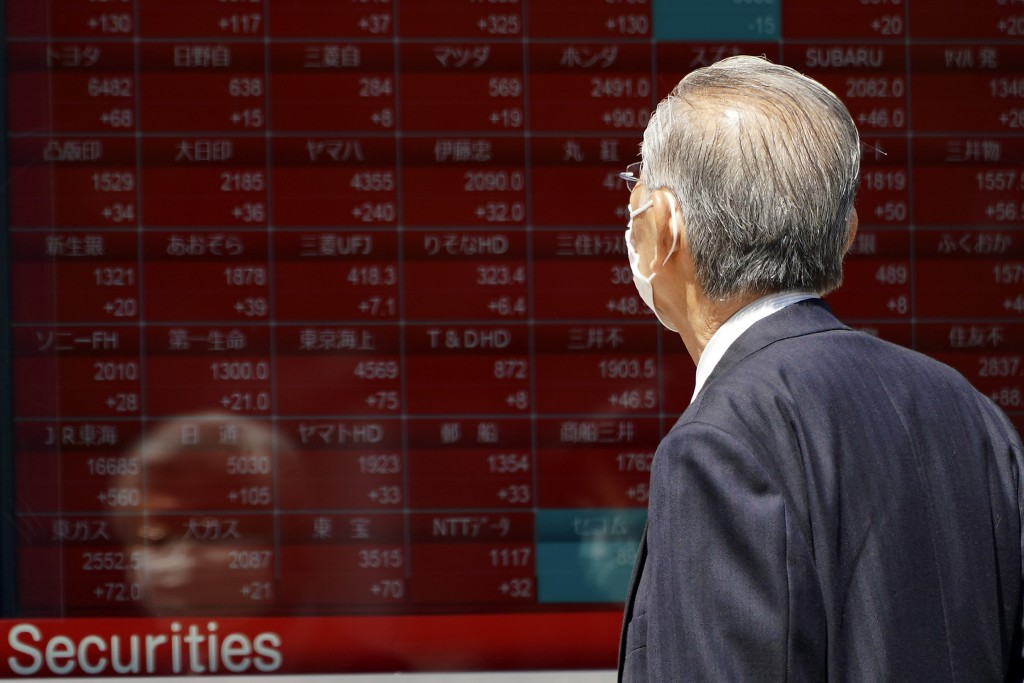 A man wearing a face mask to help curb the spread of the coronavirus looks at an electronic stock board showing Japan's Nikkei 225 index at a securiti...