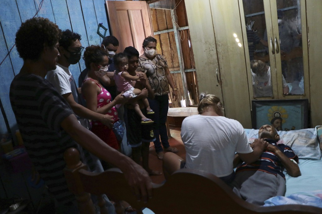 In this Thursday, April 30, 2020 photo, relatives gather around the body of Raimundo Costa do Nascimento, 86, who died in his home of pneumonia, amid ...