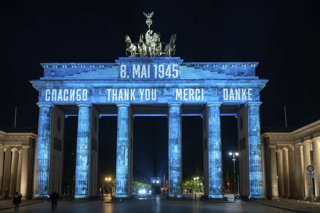 """In Russian, from left, English, French and German, the Brandenburg Gate is illuminated with the word """"Thank you,"""" during the coronavirus pandemic Frid..."""