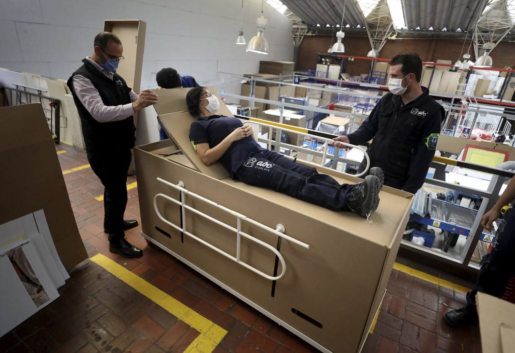 Rodolfo Gomez, left, and his employees demonstrate how their design of a cardboard box can serve as both a hospital bed and a coffin, designed for COV...