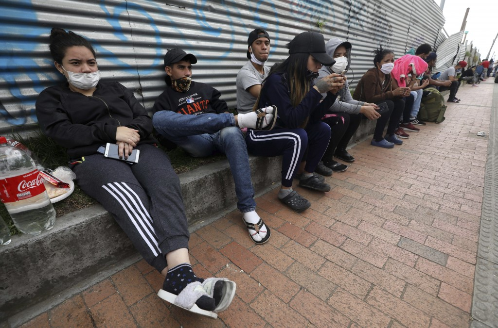 In this April 30, 2020 photo, Venezuelan migrants wait for buses that will transport them to the Venezuelan border, in Bogota, Colombia. The migrants ...