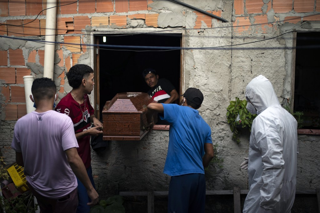 Relatives help a worker of SOS Funeral, wearing protection equipment, remove the body of Eldon Cascais, who according to the relatives had preexisting...