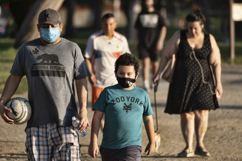 People wearing masks amid the coronavirus pandemic exercise around a track at the Van Nuys/Sherman Oaks Recreation Center, in the Sherman Oaks section...
