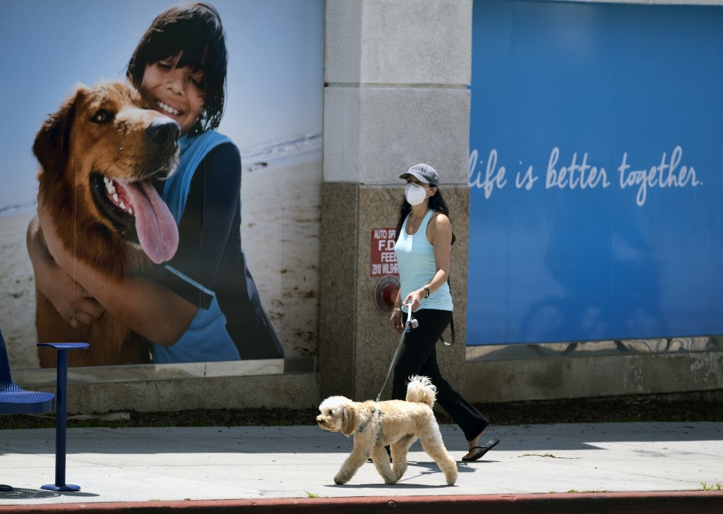 A woman wearing a protective mask for protection from the new coronavirus walks her dog in a popular shopping area in Santa Monica, Calif., on Saturda...