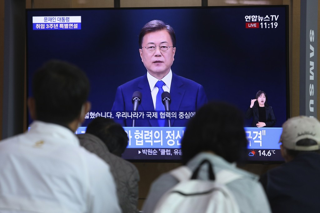 People watch a TV screen showing the live broadcast of South Korean President Moon Jae-in during a news conference to mark the third anniversary of hi...