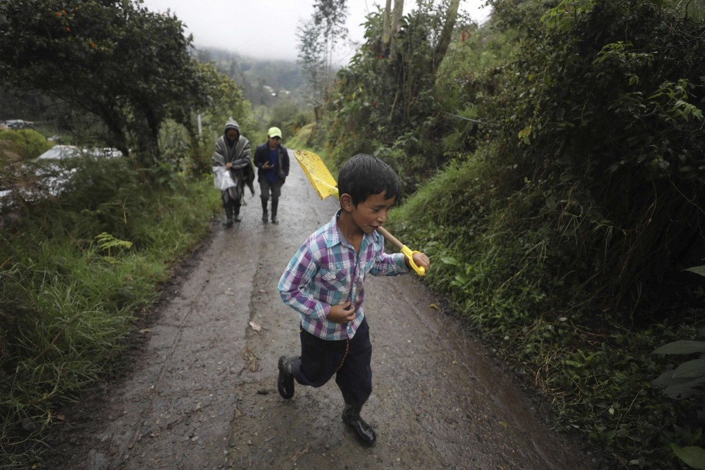 Alejandro Gaona, 9, shoulders a shovel, followed by his mother Nubia Rocio Gaona, 37, and his brother David Gaona, 14, as they walk on a road that lea...