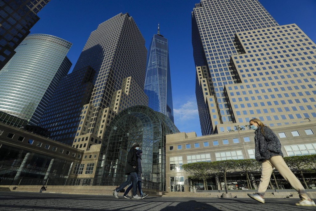 Pedestrians wear protective masks during the coronavirus pandemic as they walk past Brookfield Place Saturday, May 9, 2020, in New York. (AP Photo/Fra...