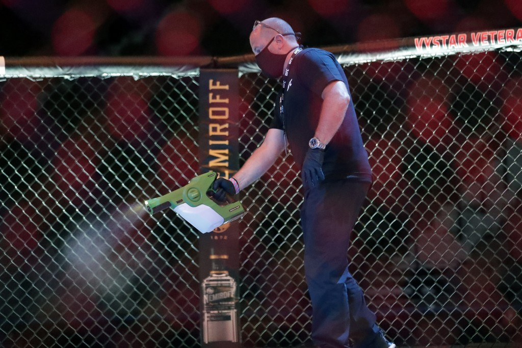 A worker sprays sanitizer in the octagon between bouts during a UFC 249 mixed martial arts competition, Saturday, May 9, 2020, in Jacksonville, Fla. (...