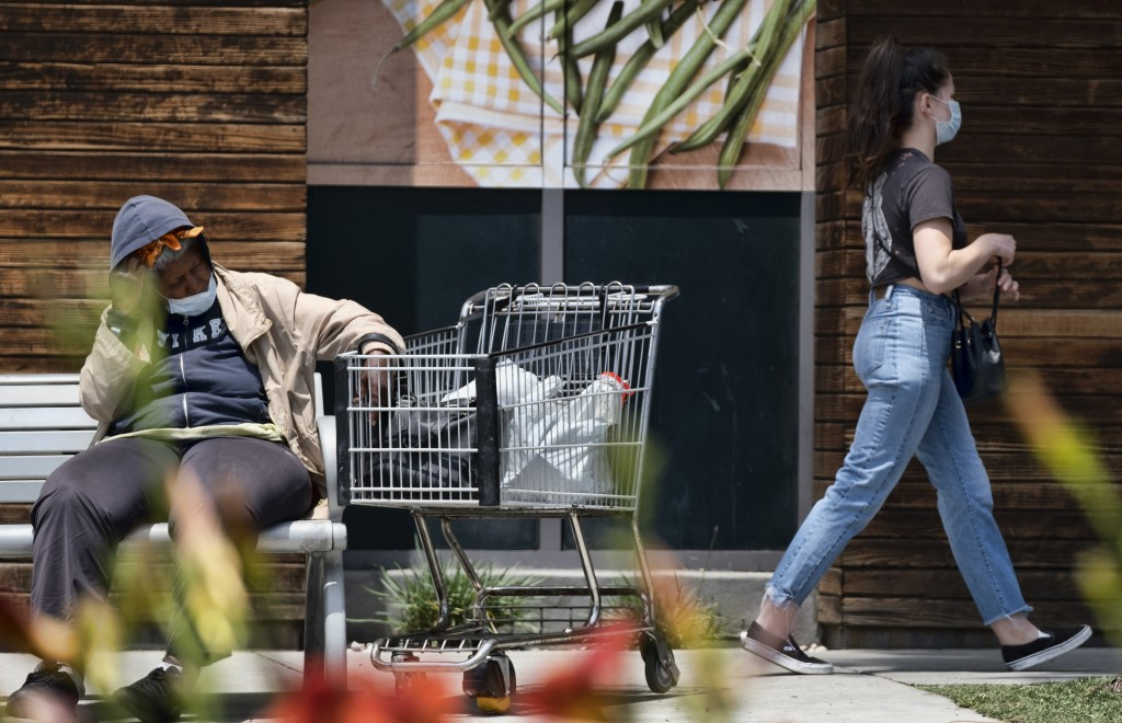 A woman sits at a bus stop with a shopping cart along a popular shopping area in Santa Monica, Calif., Saturday, May 9, 2020, during the coronavirus o...