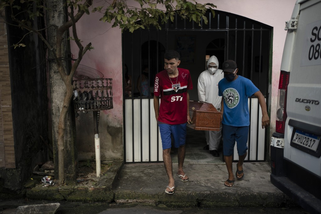 Relatives help a worker of SOS Funeral, wearing protection equipment, carry the body of Eldon Cascais, who according to them had pre-existing health c...