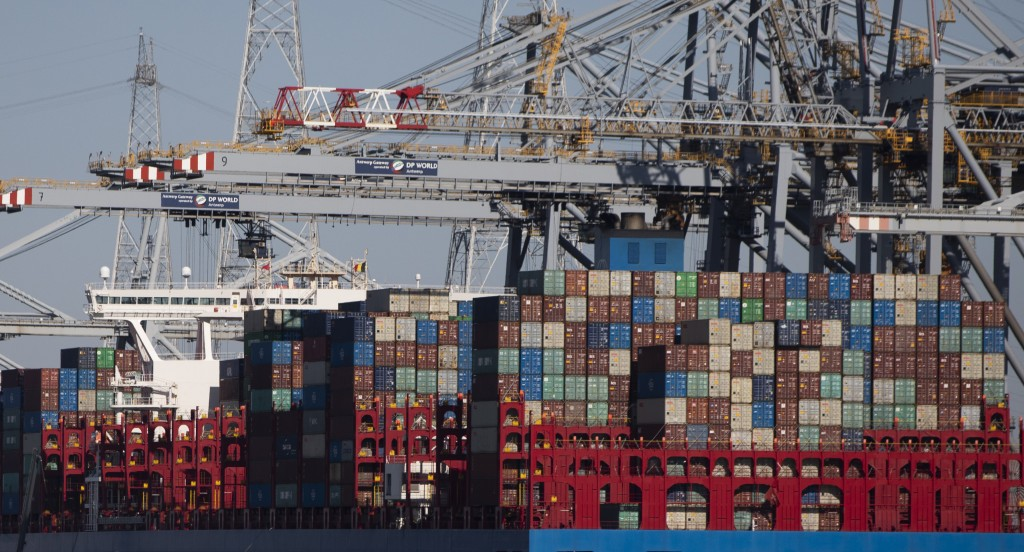In this Monday, March 23, 2020 file photo, shipping containers are offloaded from a vessel in the Port of Antwerp, Belgium. They can't expect much sym...