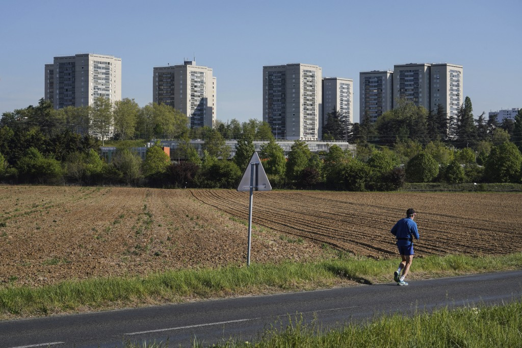 In this Wednesday, April 15, 2020 photo, a man jogs near buildings in the Minguettes district of Venissieux, a suburb of Lyon, central France. They ca...
