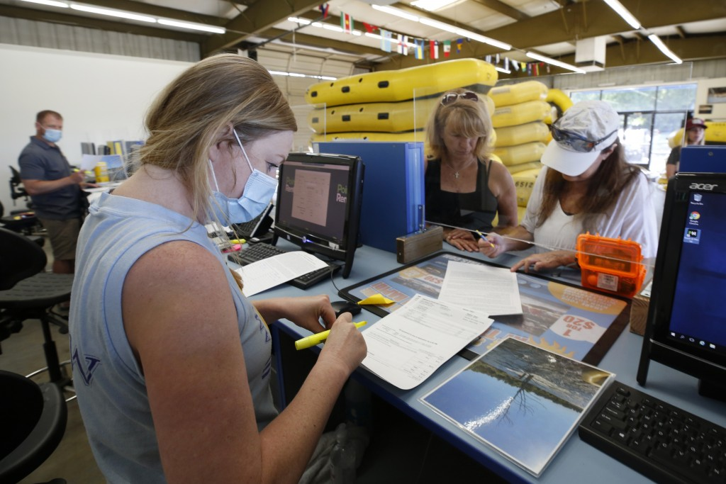 American River Raft Rentals employee Sarah Hill, left, wears a face mask and works behind a plexiglass shield as she helps customers Kathleen Doran, l...