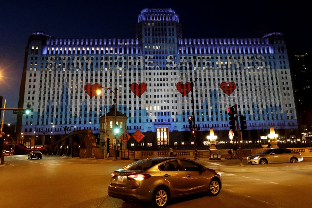 """The Merchandise Mart in downtown Chicago is lit up to read """"Stay Home Save Lives,"""" Saturday, May 9, 2020, during the coronavirus pandemic. At least 19..."""