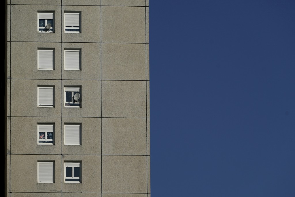 In this Wednesday, April 15, 2020 photo, a view of a building in the Minguettes district of Venissieux, a suburb of Lyon, central France. They can't e...