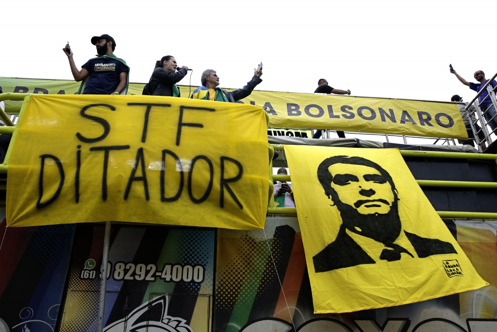 Supporters of Brazil's President Jair Bolsonaro stand above a sign referring to the Supreme Court as a dictator, and a banner depicting Bolsonaro duri...