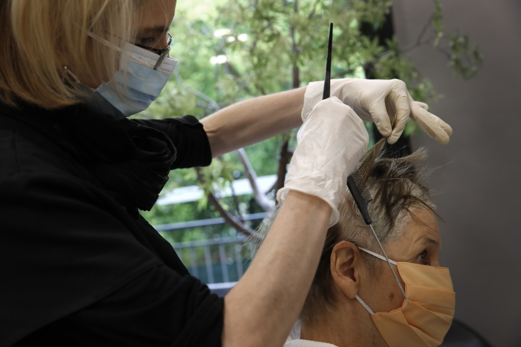A woman gets a hair cut at a hairdressing salon in Sevres, outside Paris, Monday, May 11, 2020. The French began leaving their homes and apartments fo...