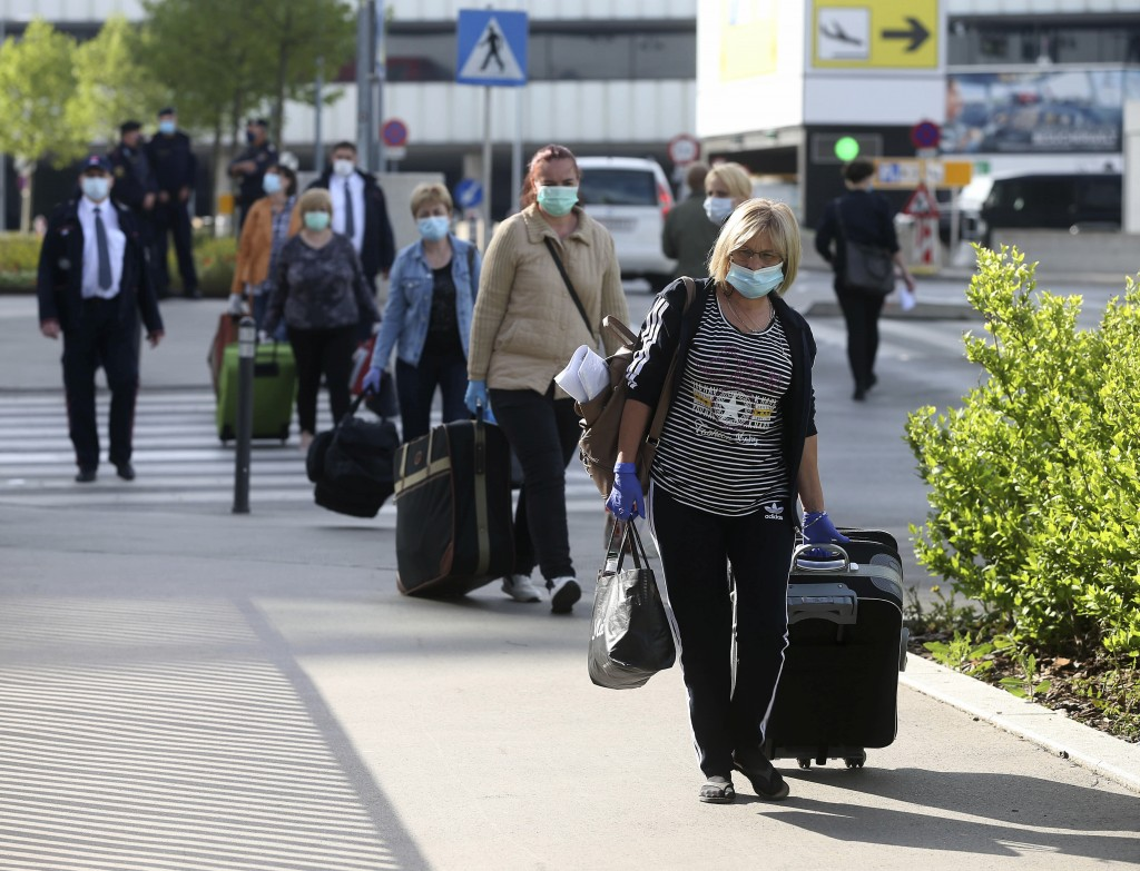 Romanian care workers with face masks accompanied by police and security arrive at the train station of Vienna's Schwechat airport, Austria, Monday, M...