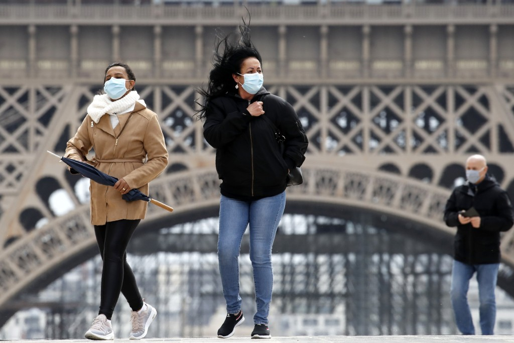Women wear a protective mask as they walk near the Eiffel Tower, in Paris, Monday, May 11, 2020. The French began leaving their homes and apartments f...