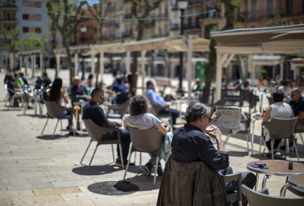 Customers sit and drink on a terrace bar in Tarragona, Spain, Monday, May 11, 2020. Roughly half of 47 million Spaniards are stepping into a softer ve...