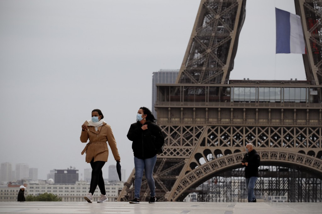 People walk near the Eiffel Tower, in Paris, Monday, May 11, 2020. The French began leaving their homes and apartments for the first time in two month...