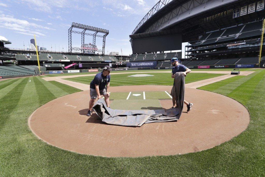 Grounds crew workers Jacob Weiderstrom, left, and Marcus Gignac pull a tarp off home plate as they continue to keep the Seattle Mariners' field in pla...