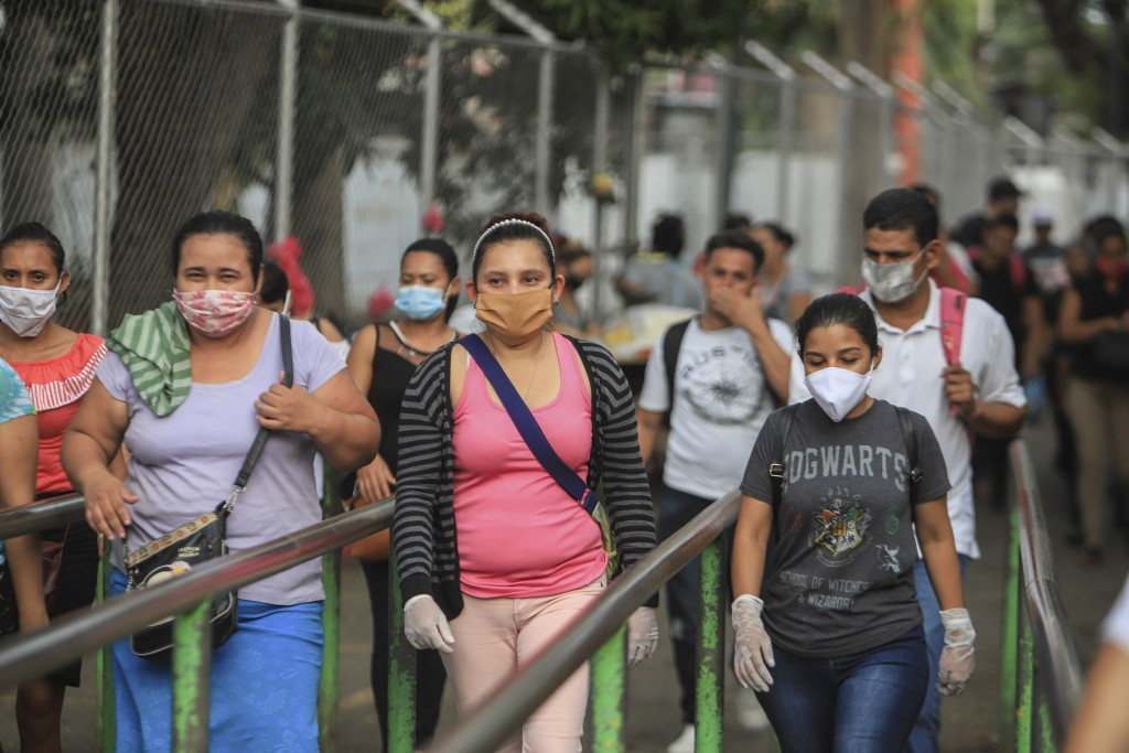 Workers wear masks as a protection against the spread of the new coronavirus as they leave from a day's work in Managua, Nicaragua, Monday, May 11, 20...