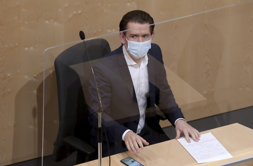 FILE - In this Wednesday, April 22, 2020 file photo, Austrian Chancellor Sebastian Kurz wears a protective mask and sits behind a plexiglass sheild du...