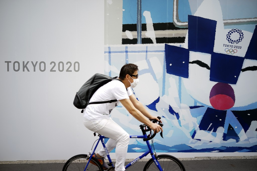 A man wearing a face mask to help curb the spread of the coronavirus rides a bicycle in front of an advertisement of Tokyo 2020 Olympic Games in Tokyo...