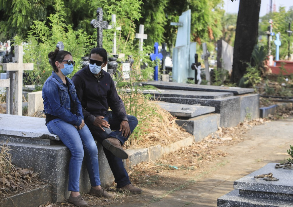 A couple wear masks as they attend a funeral at the Central cemetery of Managua, Nicaragua, Monday, May 11, 2020. President Daniel Ortega's government...