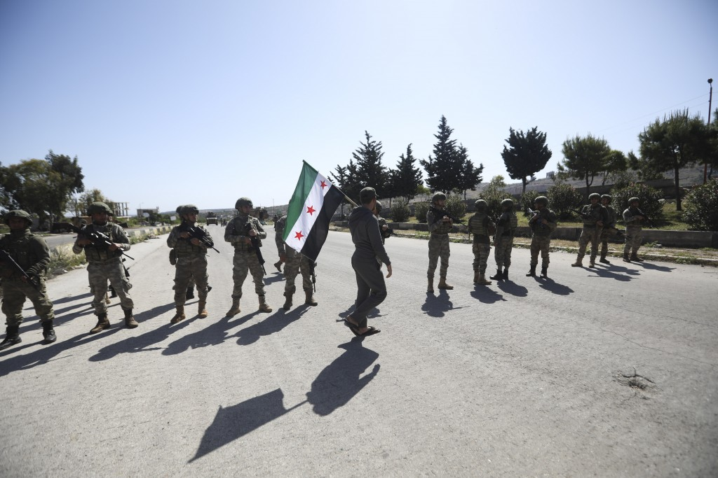 A man carries Syrian Independence flag as Turkish soldiers block a road after a nearby explosion outside the city of Ariha, in Idlib province, Syria, ...