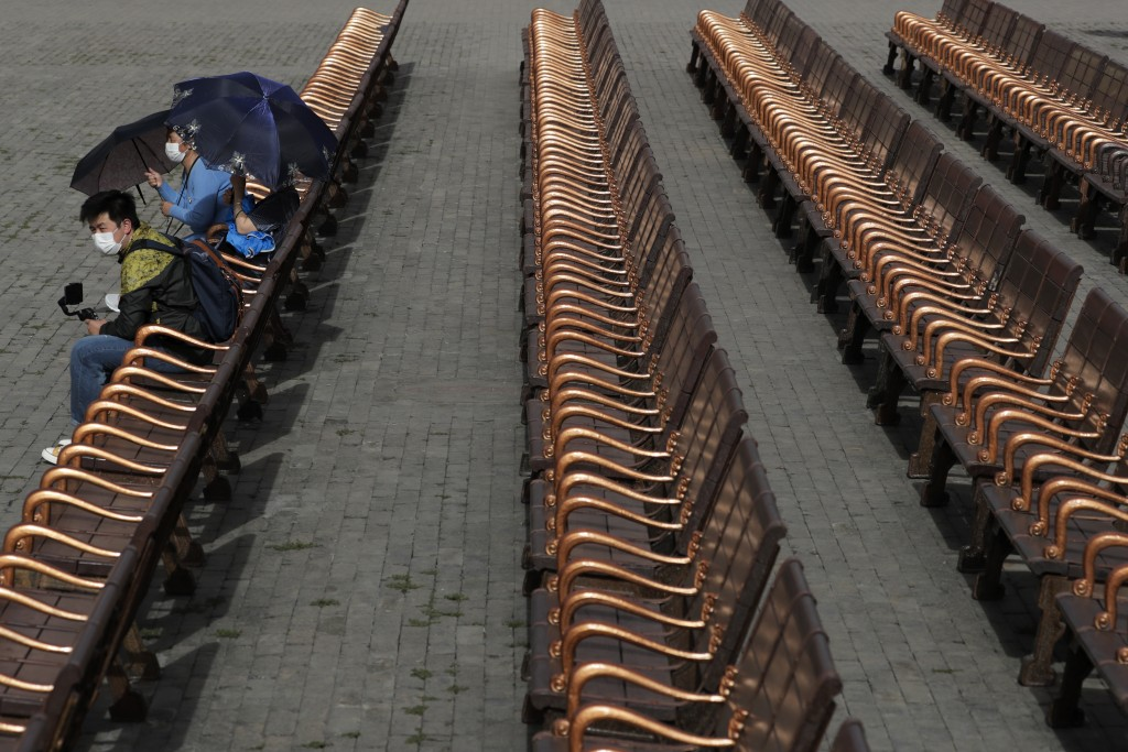 Visitors wearing protective face masks to help curb the spread of the new coronavirus take a rest on the bench at the Forbidden City in Beijing, Tuesd...