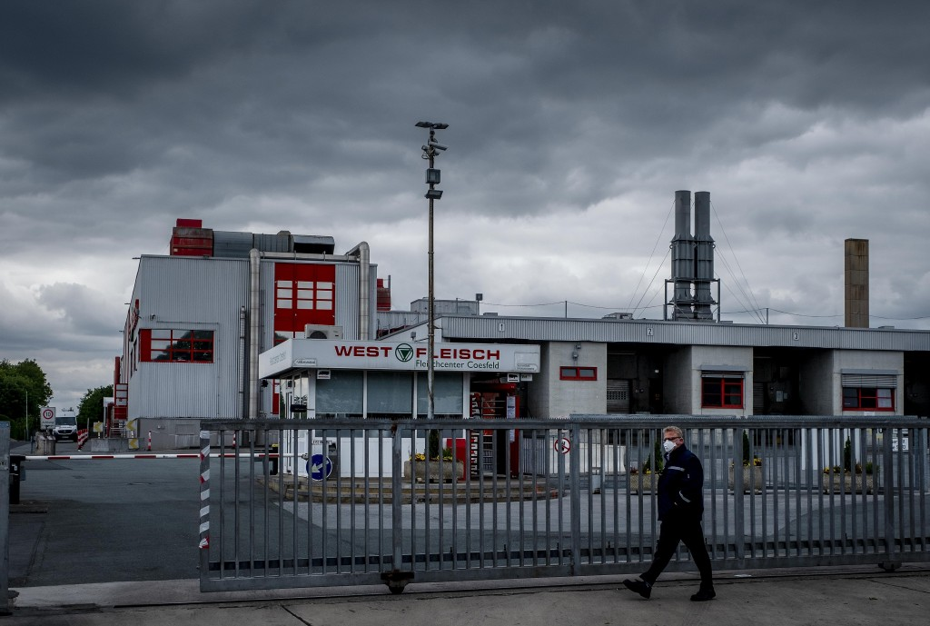 FILE - In this Tuesday, May 12, 2020 file photo a man walks past the Westfleisch slaughterhouse in Coesfeld, Germany. The German government agreed Wed...