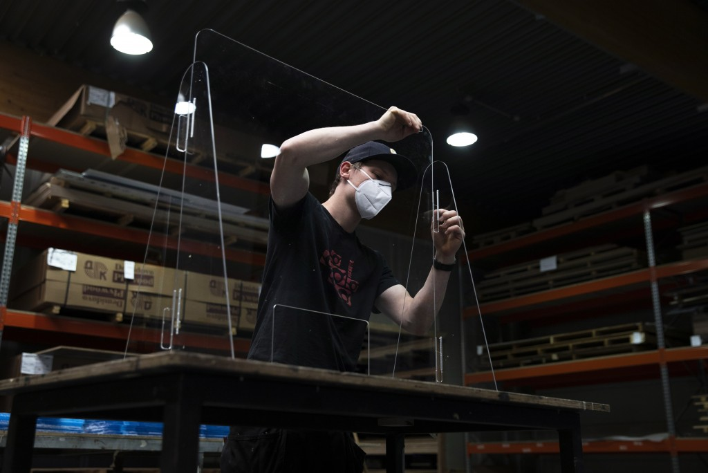 FILE - In this Monday, May 4, 2020 file photo, an employee at Fisheye in Wetteren, Belgium, assembles a plexiglass protection shield. The company has ...