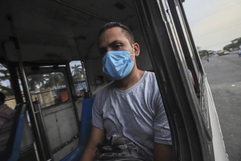 A man wears a mask against the spread of COVID-19 disease, as he rides a bus home in Managua, Nicaragua, Monday, May 11, 2020. President Daniel Ortega...