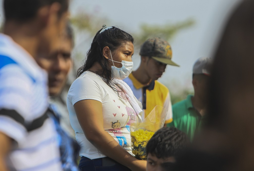 A woman wears a mask against the spread of COVID-19 disease, as she attends a funeral at the Central cemetery of Managua, Nicaragua, Monday, May 11, 2...