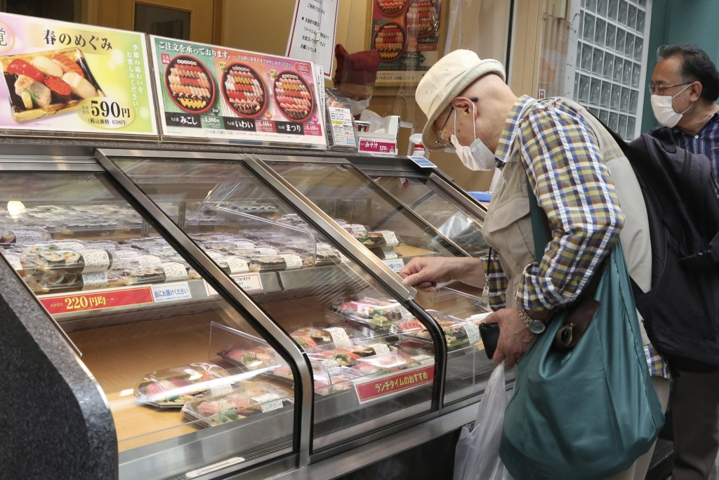 People wearing face masks to protect against the spread of the new coronavirus look at packs of sushi at a shopping area in Yokohama, near Tokyo, Wedn...