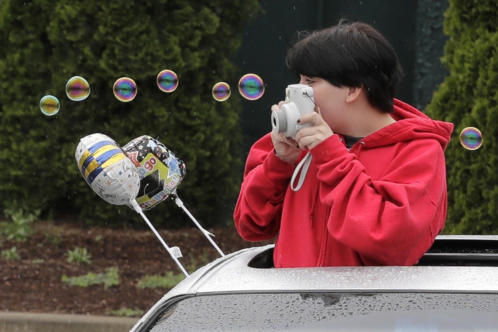 Ember Kenyon holds a camera as bubbles float through the air, Tuesday, May 12, 2020, during a drive-up car parade to distribute caps and gowns to seni...