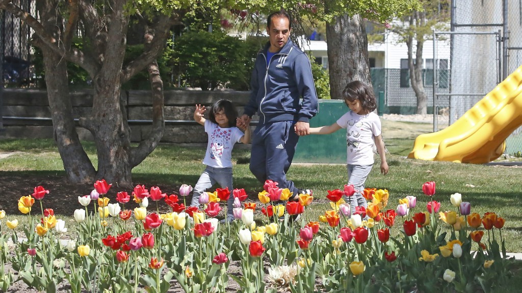 In this April 22, 2020, photo, Afghan refugee Mahmood Amiri walks with his daughters Marwa, 6 and Safa, 3, in West Valley City, Utah. Coronavirus rest...