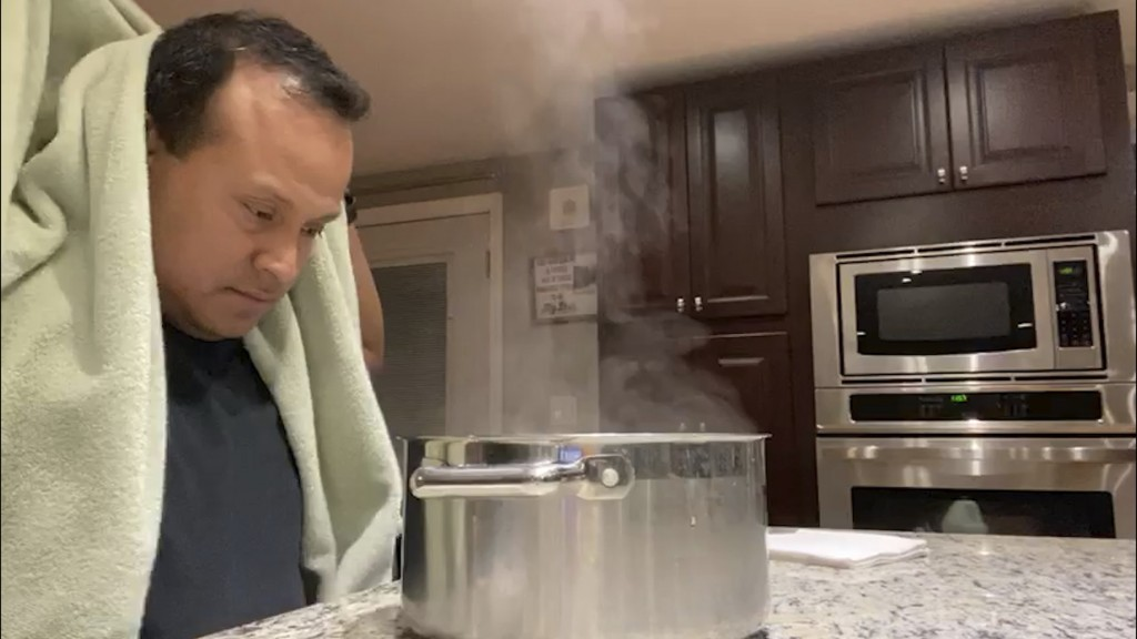 This 2020 image from video provided by Grety Melo shows her husband, Alex, using a steaming pot for a nebulizing treatment at his home in York, Maine....