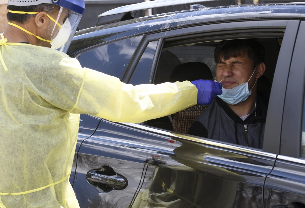 In this April 22, 2020 photo, Ganga Khadka, a refugee from Nepal, gets a test for the coronavirus in the parking lot of Dr. P.J. Parmar's clinic in Au...