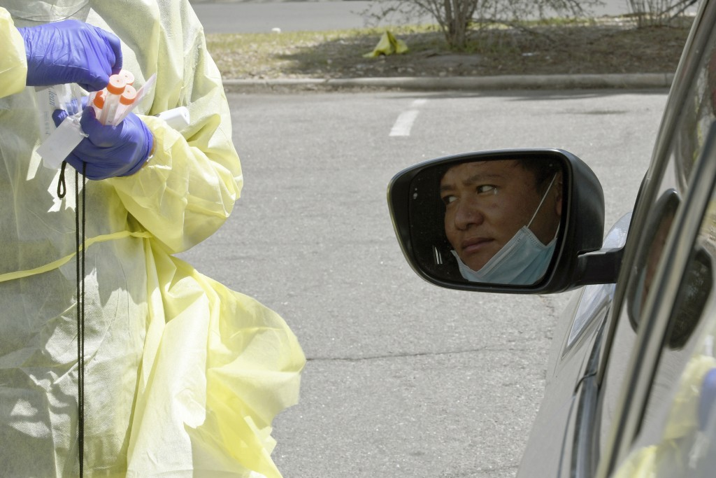 In this April 22, 2020 photo, Pramit Rai, a refugee from Nepal, waits in a car to be tested for the coronavirus at Dr. P.J. Parmar's clinic in Aurora,...