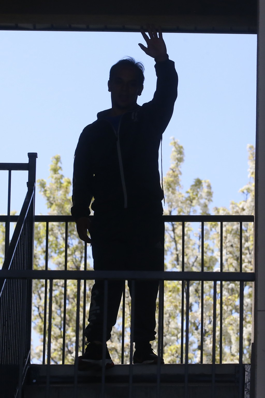 In this April 22, 2020, photo, Afghan refugee Mahmood Amiri waves from his apartment, in West Valley City, Utah. The coronavirus restrictions imposed ...
