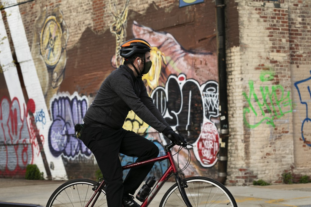 A cyclist wearing a mask passes a graffiti-covered wall in the Red Hook neighborhood of Brooklyn, Tuesday, May 12, 2020, in New York. Warning that the...